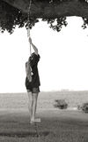 Girl on Tree Swing. A girl playing on a tree swing in the country stock photo
