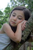 Girl in tree thinking. A portrait of a little girl resting on a tree branch, deep in thought royalty free stock photo