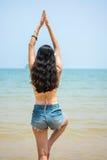 Girl in yoga tree pose on  beach Royalty Free Stock Photo