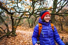 A girl with trekking sticks. A girl with trekking sticks walks along a forest trail. Skyrunning in the fall. Active recreation in nature. A woman is walking on Royalty Free Stock Images