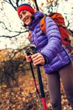 A girl with trekking sticks. A girl with trekking sticks walks along a forest trail. Skyrunning in the fall. Active recreation in nature. A woman is walking on Stock Photo