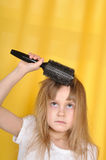 Girl treying to brush her hair Royalty Free Stock Photo