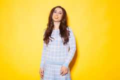 Girl tricked bubble of chewing gum. Girl in a blue dress chews gum Stock Images