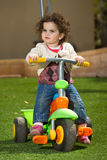 Girl on tricycle stock photo