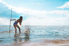 Girl with a trident in his hand looks at the sea surface Stock Images