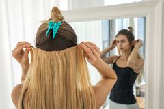 Girl tries on blonde false hair strands on clips. Artificial hair extension stock photography