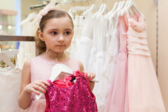 Girl tries on a bright red dress in the store Stock Images