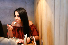 Girl tries desert and sits at table, listens to and talks with f Stock Images