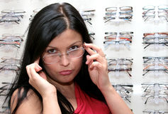 The girl tries on glasses Royalty Free Stock Photos