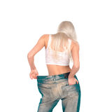 The girl tries on jeans. Girl blonde tries on jeans a very large size Royalty Free Stock Images