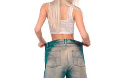 The girl tries on jeans. Girl blonde tries on jeans a very large size Royalty Free Stock Photos