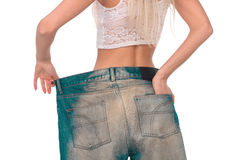 The girl tries on jeans. Girl tries on jeans a very large size Royalty Free Stock Photos