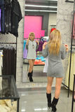 Girl tries on a new dress in the shop front of a mirror Stock Photo
