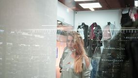 Girl tries on a new stylish sweater in the store. View through the window. Shopping stock video