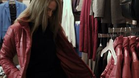The girl tries on a red jacket stock footage