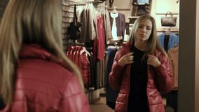 The girl tries on a red jacket stock video
