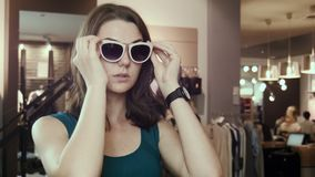 The girl tries on sunglasses stock video footage
