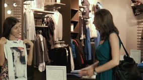 The girl tries on a T-shirt in shop stock video footage
