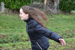 Girl tries to fly in the storm. Stormy weather, teenage girl outside she has fun and tries to fly with wide spread arms Stock Photos