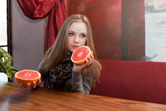 Girl tries to half of red grapefruit Stock Images