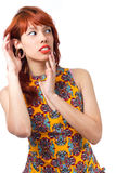 Girl tries to listen to something carefully. Young redhead woman Stock Images