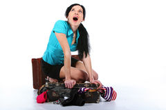 Girl tries to place clothes in an old suitcase Royalty Free Stock Photos