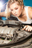 Girl tries to repair broken car Royalty Free Stock Photos