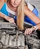 Girl tries to repair broken car Stock Photos