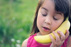 The girl tries to speak by means of a banana instead of phone. Close up portrait of little caucasian girl with closed eyes tries to speak by means of a banana royalty free stock photos