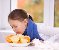 Girl tries to taste a slice of orange Royalty Free Stock Photo