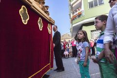 Girl tries to touch the skirt of the throne to have good luck, popular tradition in Andalusia, Easter procession on Holy Thursday,. Linares, Jaen province, SPAIN Royalty Free Stock Photo