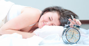 The girl tries to ungear an alarm clock Royalty Free Stock Photos