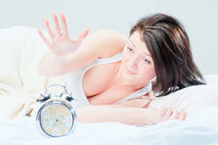 The girl tries to ungear an alarm clock Royalty Free Stock Photography