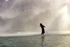 Girl in the Trocadero fountains by the Eiffel Tower. Summer Heat wave in the greater Paris. Stock Photos