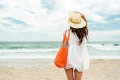 Girl on a tropical beach relaxing. Woman in straw hat and white dress on a tropical beach with orange bag Stock Photos