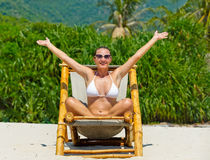 Girl on a tropical beach sitting at chaise lounge Stock Photography