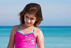 Girl on a tropical beach with sun cream Royalty Free Stock Image