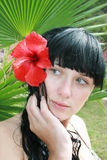 Girl with tropical flower. Palms in background Stock Image
