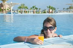 Girl in tropical pool with  orange juice Stock Photo