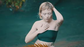 Girl in tropical rain forest jungle. Beautiful fashion girl posing, body and face covered with mud in tropical rain forest jungle near waterfall pond. Portrait stock footage