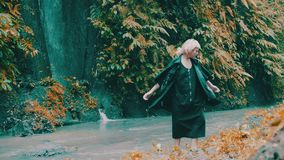 Girl in tropical rain forest jungle. Beautiful fashion girl posing in tropical rain forest jungle near the waterfall. Portrait of stylish hipster female outdoor stock video footage