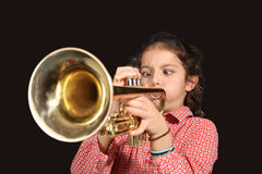Girl with trumpet. Young girl with a trumpet posing on a dark background Royalty Free Stock Photography