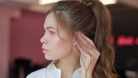 Girl try on earrings. In the beauty salon stock footage