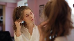 Girl try on earrings. In the beauty salon at mirror stock video footage