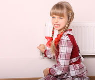 Girl try open thermostat. Royalty Free Stock Photo
