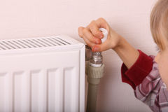 Girl try open thermostat. Royalty Free Stock Photos