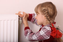 Girl try open thermostat. Crisis. Royalty Free Stock Photo