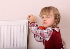 Girl try open thermostat. Crisis. Royalty Free Stock Images