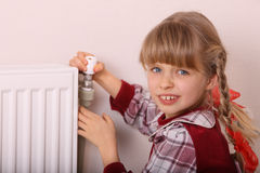 Girl try open thermostat. Crisis. Stock Photo