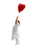 Girl try to fly. Little girl try to fly with red balloon over white stock image